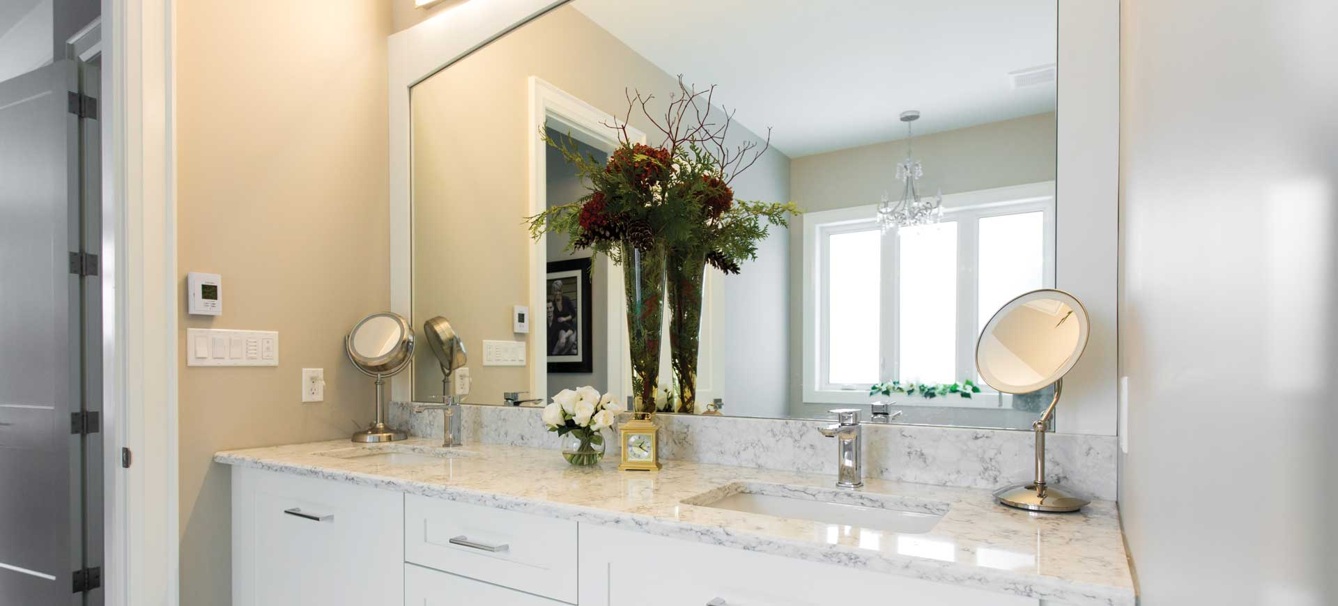 white bathroom vanity with marble countertop and backsplash