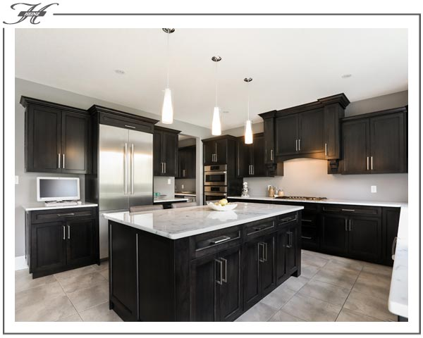 Dark Wood Cabinets And Island In Kitchen. Marble Countertop.