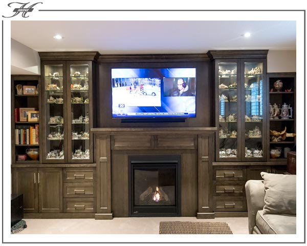 dark wood entertainment unit with curio cabinets on sides