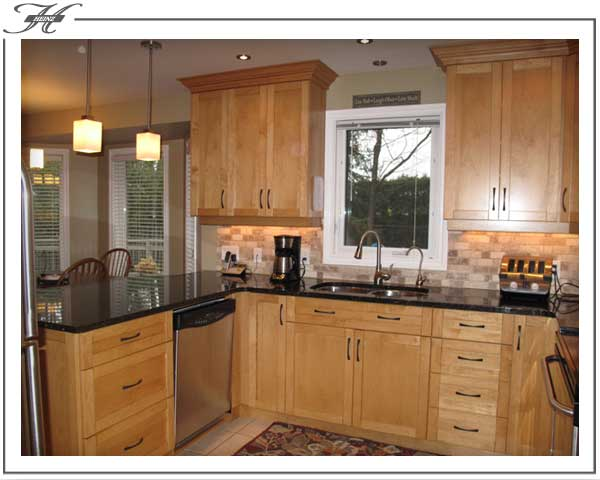 golden coloured wood kitchen cabinets with black countertop